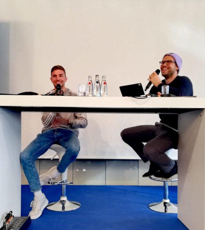 zwei junge Männer mit Mikrofon sitzend am weißen Tisch auf Barhocker und sprechen