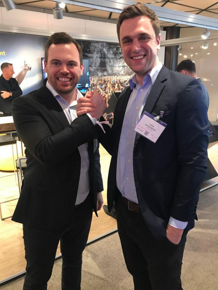 zwei Männer strahlend in die Kamera lächelnd mit Handschlag