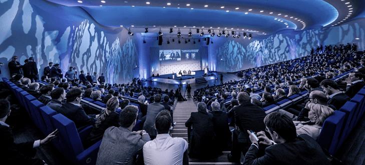 blauer Hörsal mit zentrierter Bühne und vielen Menschen
