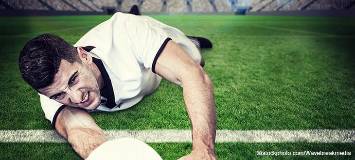 Fußballer liegt auf dem Spielfeld mit Ball